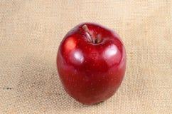Красное яблоко на дерюге Стоковые Фото