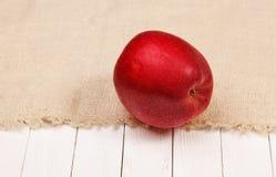 Красное яблоко на мешковине и белой таблице Стоковое фото RF