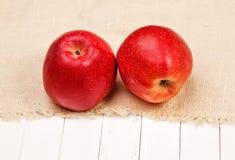 Красное яблоко на мешковине и белой таблице Стоковое Изображение