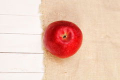 Красное яблоко на мешковине и белой таблице Стоковые Изображения