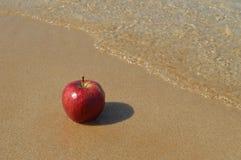 Красное яблоко на песчаном пляже Стоковая Фотография RF