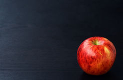 Красное яблоко на черной деревянной предпосылке Стоковое фото RF