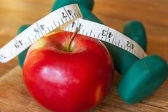 Красное яблоко, рулетка и гантели Стоковое Изображение