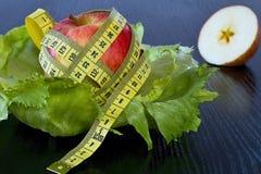 Красное яблоко с измеряя лентой на листы салата льда Стоковые Изображения