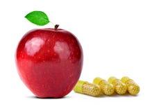 Красное яблоко с пилюльками капсулы витаминов Стоковые Фото