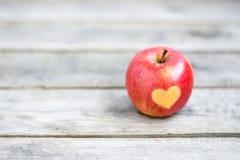 Красное яблоко с формой сердца на серой деревянной предпосылке Стоковые Изображения
