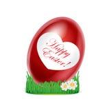 Красное яичко с счастливым сообщением пасхи в изолированной траве Стоковая Фотография