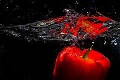 Красное papper упало в воду стоковая фотография