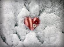 Красное striped сердце на предпосылке снежка Стоковые Изображения