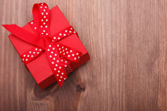 Красной лента связанная подарочной коробкой красная на деревянном столе Стоковые Изображения RF