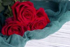 3 красной розы на зеленой ткани на белой деревянной предпосылке Стоковая Фотография