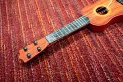 Краснокоричневая пластичная гавайская гитара с сломленными строками на floo красного ковра стоковые изображения rf