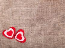 2 красно-белых сердца на увольнении, в угле левого дна Стоковая Фотография