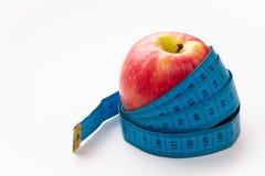 Красно-желтое Яблоко и сантиметр на ем на белой предпосылке, концепции диеты стоковая фотография rf