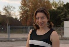 Красно-наблюданная женщина с зелеными глазами усмехаясь на камере стоковое изображение rf