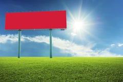 Красные афиши на зеленом поле стоковая фотография