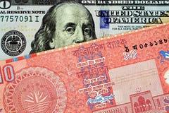 Красные бангладешские 10 принимают примечание с американской 100 долларовыми банкнотами стоковые фото