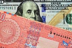 Красные бангладешские 10 принимают примечание с американской 100 долларовыми банкнотами стоковые фотографии rf