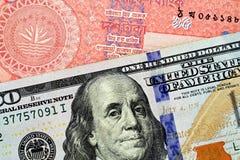 Красные бангладешские 10 принимают примечание с американской 100 долларовыми банкнотами стоковое изображение
