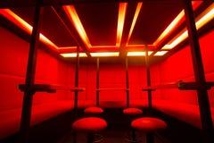 Красные барные стулы на свете цвета диода Стоковые Фото
