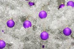 Красные безделушки на серебряной искусственной рождественской елке Стоковое фото RF