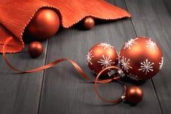 Красные безделушки рождества связанные с лентой и красной салфеткой на древесине Стоковые Изображения