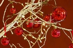 Красные безделушки вися от украшенной рождественской елки Стоковые Изображения RF