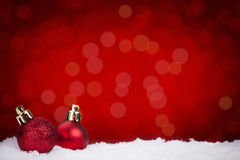 Красные безделушки рождества на снеге с красной предпосылкой Стоковое Фото