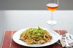 Красные бокал и макаронные изделия, спагетти с авокадоом стоковое изображение