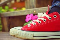 Красные ботинки на деревянном поле - тапки Стоковые Фотографии RF