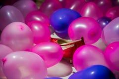 Красные ботинки спрятанные в предпосылке воздушных шаров Стоковые Изображения