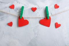 Красные бумажные сердца вися на зажимки для белья на веревочке Стоковое Изображение