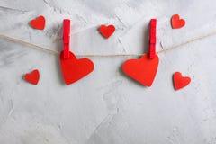 Красные бумажные сердца вися на зажимки для белья на веревочке Стоковое фото RF
