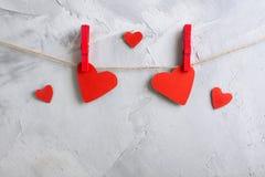Красные бумажные сердца вися на зажимки для белья на веревочке Стоковые Изображения