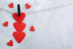Красные бумажные сердца вися на зажимки для белья на веревочке Стоковые Фотографии RF