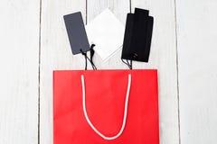 Красные бумажные хозяйственная сумка и ярлыки на деревянной предпосылке Shoppi Стоковые Фото