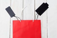 Красные бумажные хозяйственная сумка и ярлыки на деревянной предпосылке плоский l Стоковое Изображение RF