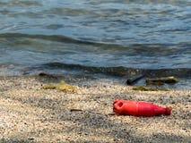 Красные бутылки содовой которые были выведены туристами на пляж стоковые фотографии rf
