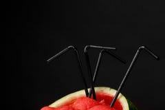 Красные ветроуловители арбуза с соломами на черной предпосылке Здоровый, свежий и красивый арбуз Вкусные соки лета скопируйте кос Стоковые Фотографии RF