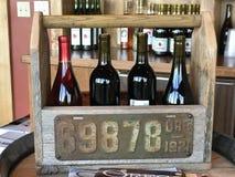 Красные вина на дисплее в деревянной несущей на винодельню Риджа меток Стоковые Фото