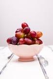Красные виноградины в розовом шаре на белой винтажной таблице Стоковое Фото
