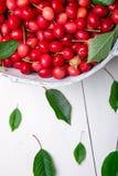 Красные вишни в белой корзине на белой деревянной предпосылке поднимающее вверх вишни близкое Стоковые Изображения