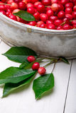 Красные вишни в белой корзине на белой деревянной предпосылке поднимающее вверх вишни близкое Стоковая Фотография RF