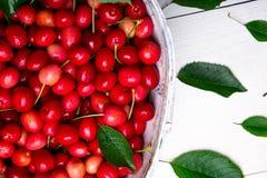 Красные вишни в белой корзине на белой деревянной предпосылке поднимающее вверх вишни близкое Взгляд сверху Стоковые Фото