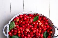 Красные вишни в белой корзине на белой деревянной предпосылке поднимающее вверх вишни близкое Взгляд сверху Стоковые Изображения RF
