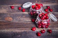 Красные вишни в стеклянном опарнике на темной деревянной предпосылке с космосом экземпляра Солнечное лето и концепция сбора E Стоковое Изображение RF