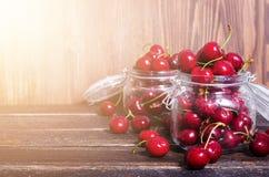 Красные вишни в стеклянном опарнике на темной деревянной предпосылке с космосом экземпляра Солнечное лето и концепция сбора E Стоковая Фотография
