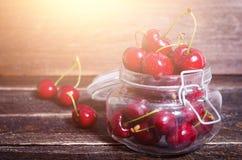 Красные вишни в стеклянном опарнике на темной деревянной предпосылке с космосом экземпляра Солнечное лето и концепция сбора E Стоковые Фото