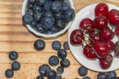 Красные вишни и голубики ягод с деревенской деревянной предпосылкой стоковые фото