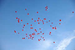 Красные воздушные шары при листы летая в голубое небо Стоковое Изображение